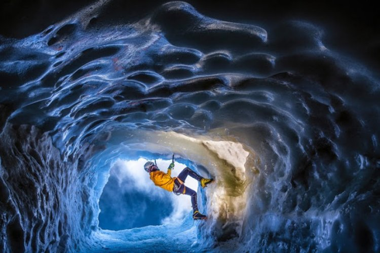 احد الافراد يمارس هواية التسلق في كهف الجليد
