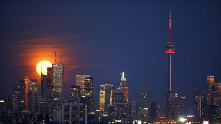 صعود القمر خلف برج وكالة الأنباء الكندية في تورونتو