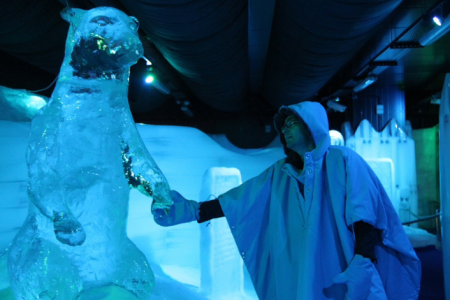 أحد زوار متحف الثلج يرتدي لبس الاسكيمو ويلتقط صورة لنفسه